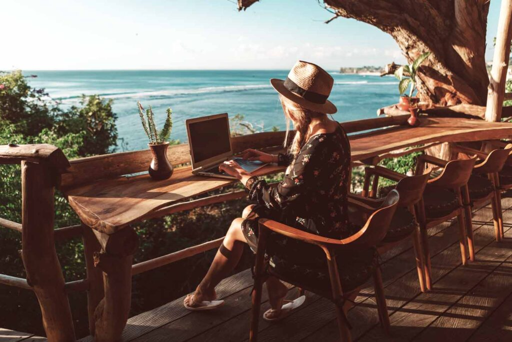 a young woman working on her laptop facing the ocean